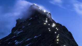"""Lamps illuminate the path of the first ascent on the Matterhorn mountain, seen from the Hoernli mountain hut, in Zermatt, Switzerland, Late Monday, July 13, 2015. Authorities in Switzerland have declared the iconic Matterhorn mountain off-limits for a day on Tuesday, July 14, 2015, on the 150th anniversary of the first ascent. The so-called """"Matterhorn silence"""" is intended to honor more than 500 climbers who have died trying to reach the top. (Dominic Steinmann/Keystone via AP)"""